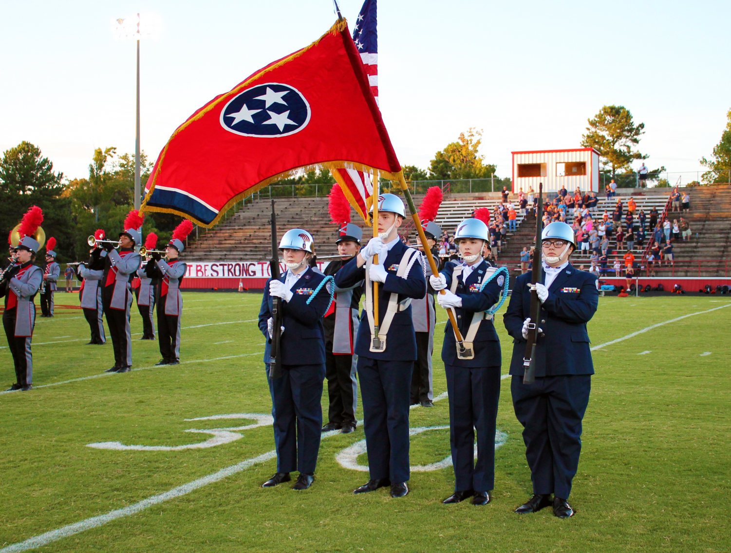 Left to right cadets Madison Cox, Oren Harper, Kinsey York, and Tabby Syferd presenting the colors at a football game