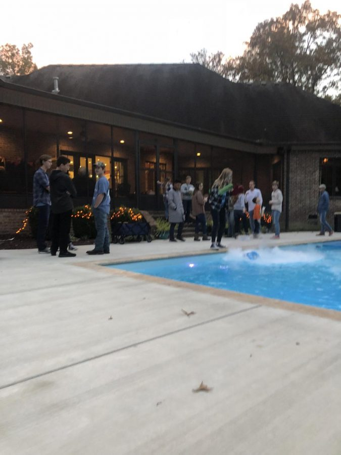Elizabeth Proffitt pours dry ice into the pool to kick off a spooky night of fun.