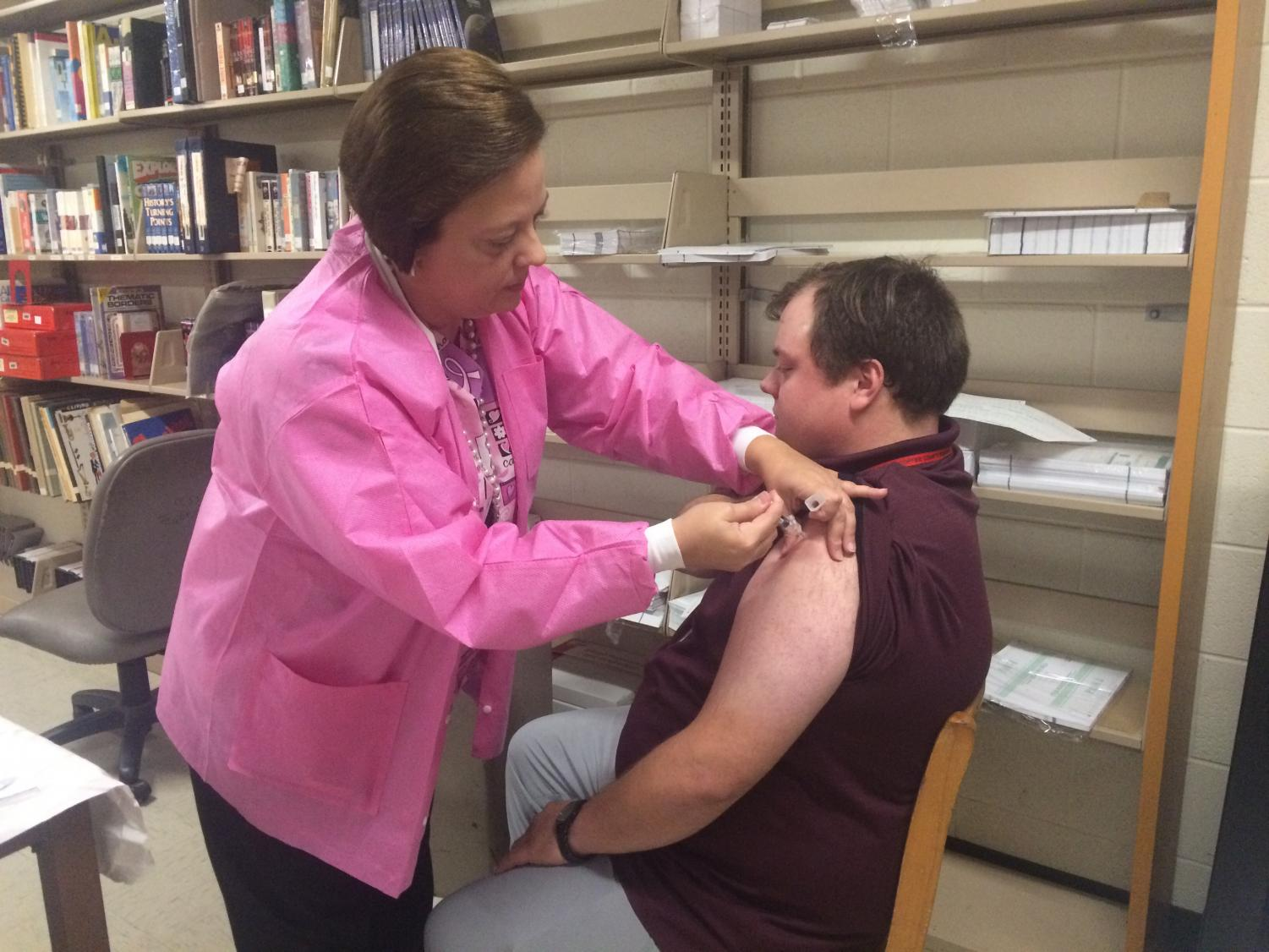 Mr. King receives a dose of the flu shot.