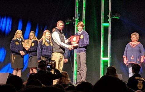 Josh Barnard receives his award for winning the extemporaneous speech contest at the FFA convention.