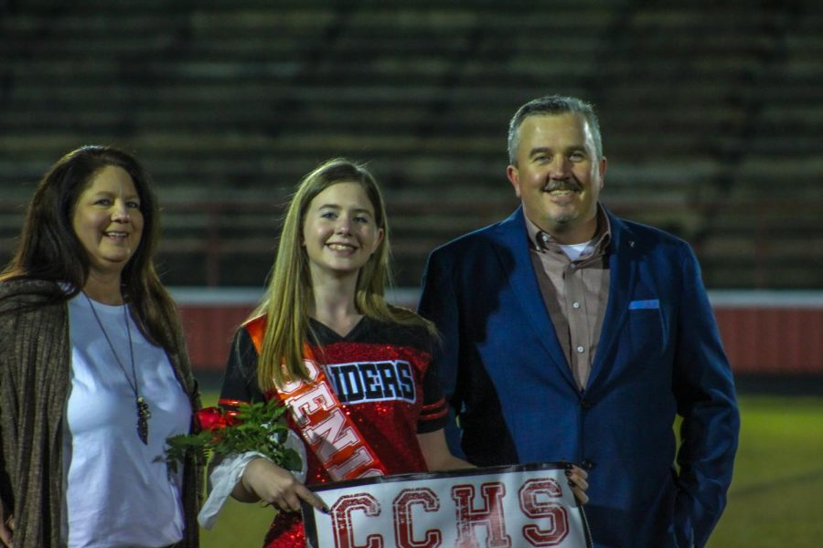 Hannah Grimes, a dance team member, stands with her family at Senior Night.