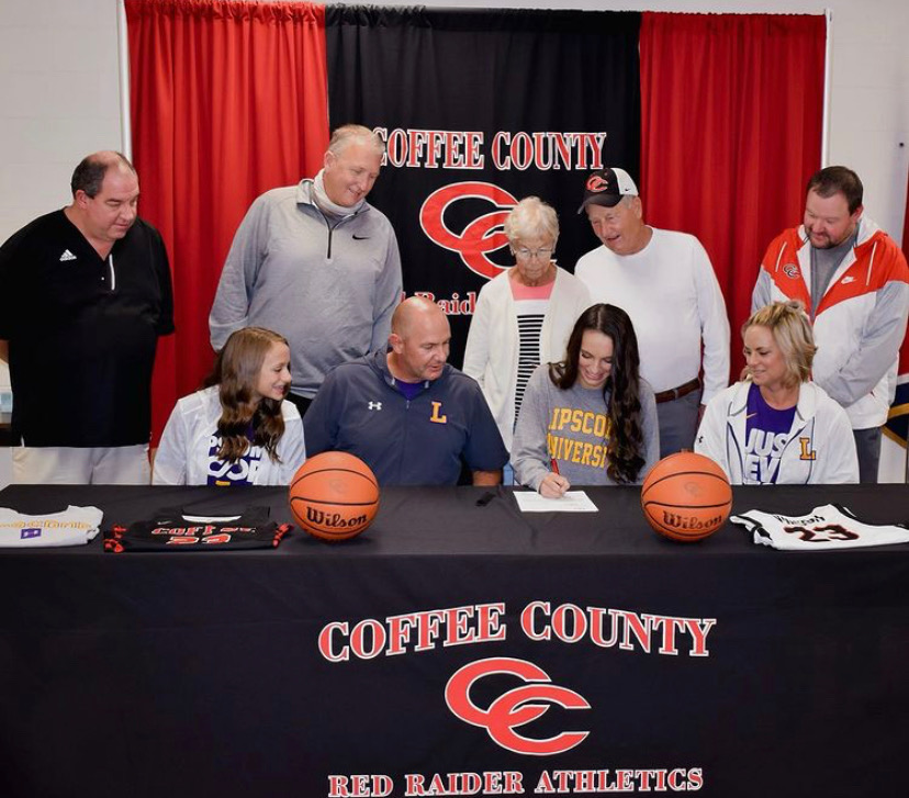 Bella Vinson and her guests watch her sign for Lipscomb University.