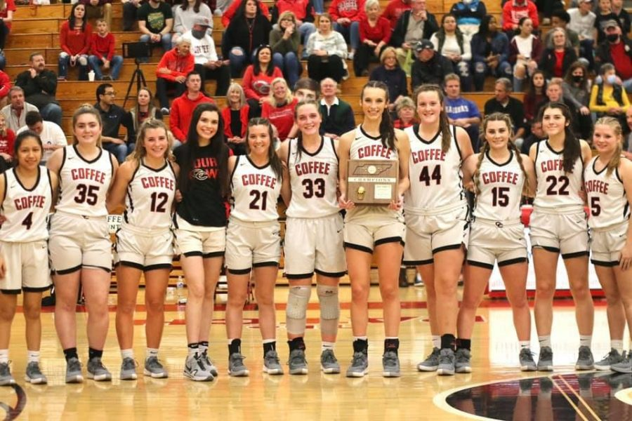 The girls team raising the District Championship plaque.