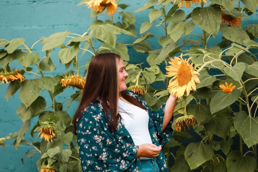 Bailey Crosslin, in a photo session with Jessica Helton Photography, poses with a few sunflowers that are almost as radiant as her!