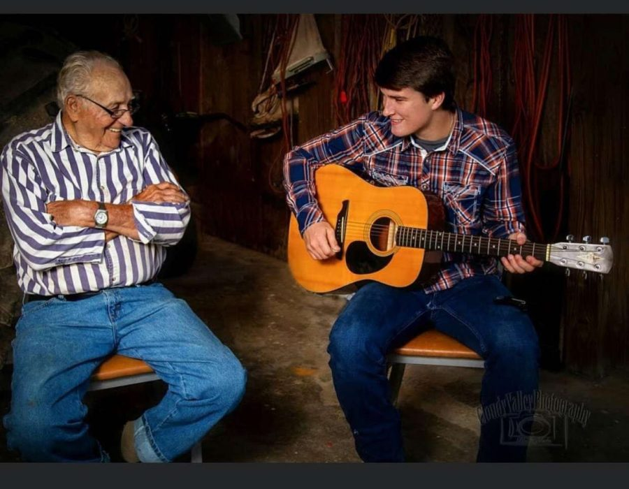 Spry playing the guitar with his grandpa, O'Neil Spry.