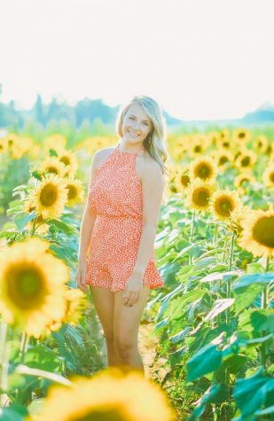 Kylie standing in a field of flowers.