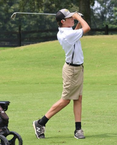 Daugherty tries to hit a 6 iron on the green at the Raiders' first home golf match at Willowbrook Golf Course.