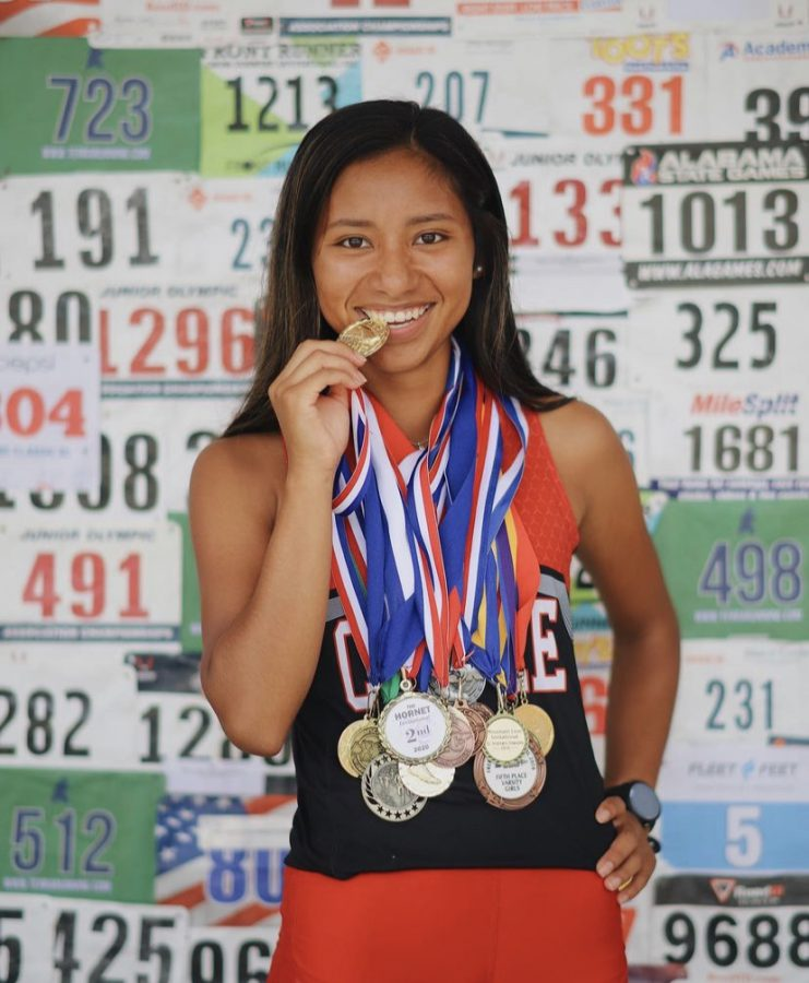 Patrica poses with the medals she has received over the years.