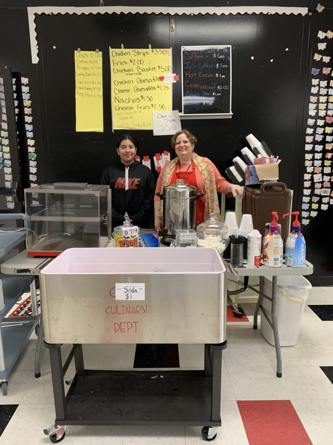 Mrs. Louden and a culinary student standing at their FACs fundraising booth.