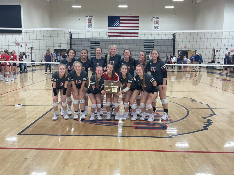 The team smiles big with their district championship plaque.